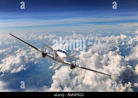 Airplane flying high above the clouds - Stock Photo