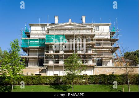 Scaffolding erected around a grand house undergoing renovations, London, England, UK - Stock Photo