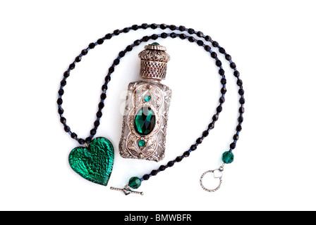 Glass crystal green heart necklace with silver  and green filigree perfume bottle. - Stock Photo