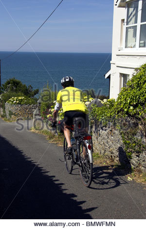 A cyclist on National Cycle Route 8 passing through Llanaber, near Barmouth, Wales, UK. - Stock Photo