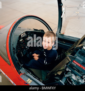 A young boy sits in BAE Systems Hawk cockpit of the 'Red Arrows', Britain's Royal Air Force aerobatic team. - Stock Photo