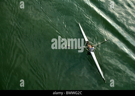 image of a young man rowing in kayak down the river - Stock Photo