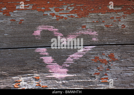 pink heart painted on park bench - Stock Photo