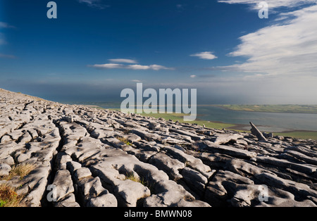Limestone pavement, on Abbey Hill, the Burren, Co Clare, overlooking Aughinish Island in Galway Bay, Ireland - Stock Photo