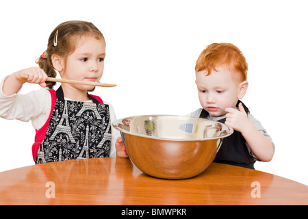 Kids making cake in large mixing bowl. Isolated on white. - Stock Photo