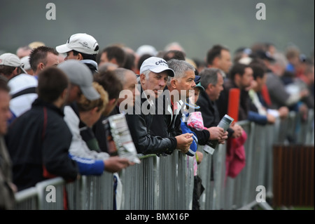 Golf fans watch players on the practice range at The Celtic Manor Wales Open golf tournament - Stock Photo