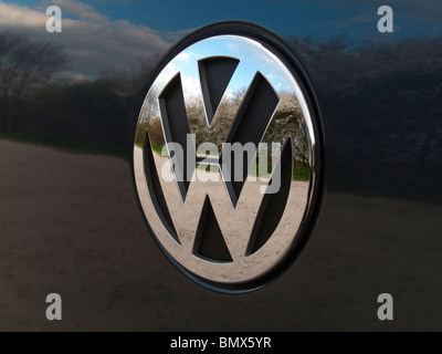 Close up view of a chrome Volkswagen VW logo on a car with reflections - Stock Photo