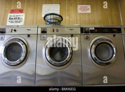 three washing machines inside a public laundrette - Stock Photo