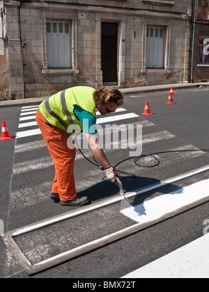 Roadworker repainting pedestrian crossing stripes on road surface - France. - Stock Photo