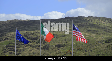 The flags of the EU, Irish Republic and USA fly over County Kerry in the Irish Republic. - Stock Photo