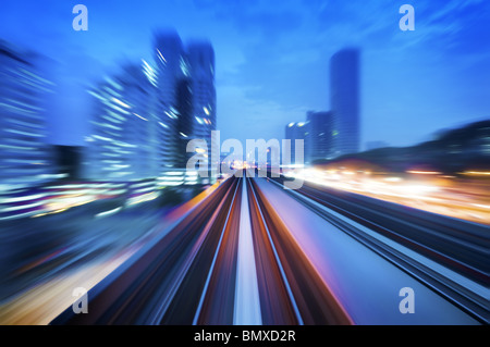 High speed train passing in between Kuala Lumpur City during dusk hour. Focus on the rail road. - Stock Photo