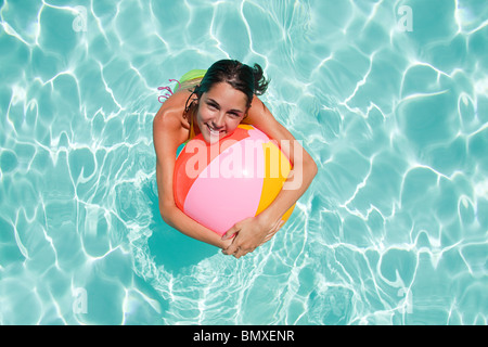 swimming pool beach ball background. Young Woman In Swimming Pool With Beach Ball - Stock Photo Background