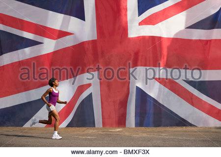 Woman running past british flag - Stock Photo