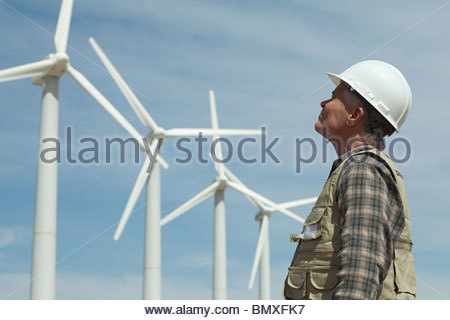 Man in hard hat looking at wind turbines - Stock Photo