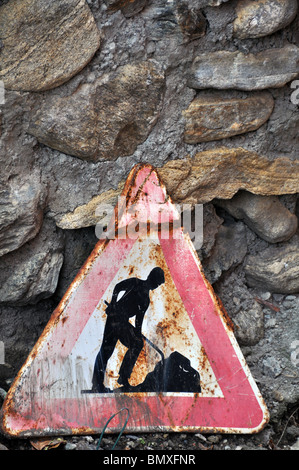 Old, rusty roadworks sign in front of rough and ancient stone wall - Stock Photo