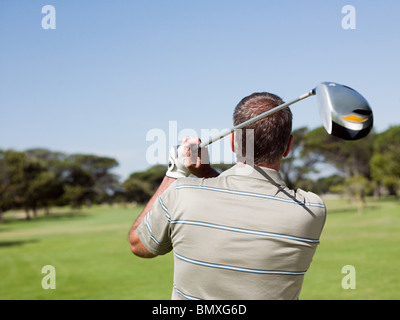 Man playing golf on golf course - Stock Photo