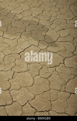 Cracked surface of dry lake bed with shadow - Stock Photo
