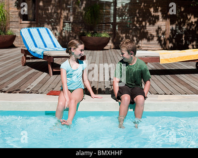 Boy and girl on edge of swimming pool - Stock Photo