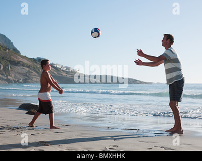 Father and son playing ball on a beach - Stock Photo