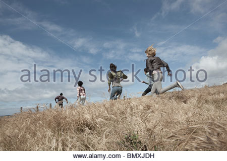 Group of young friends running in field - Stock Photo