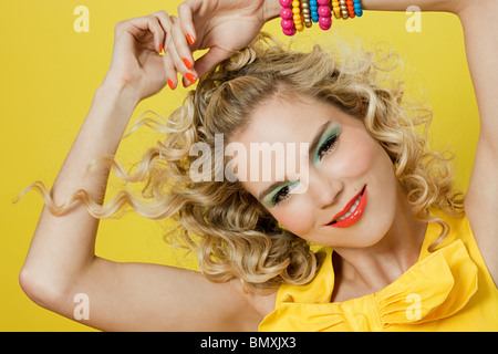 Young blonde woman against yellow background - Stock Photo