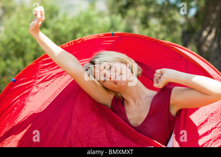 woman waking up in tent - Stock Photo
