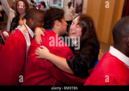 Hispanic boy hugs well-wisher after graduation ceremony from KIPP Academy high school in Houston, Texas, USA