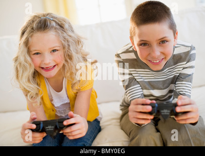 Siblings playing video game - Stock Photo
