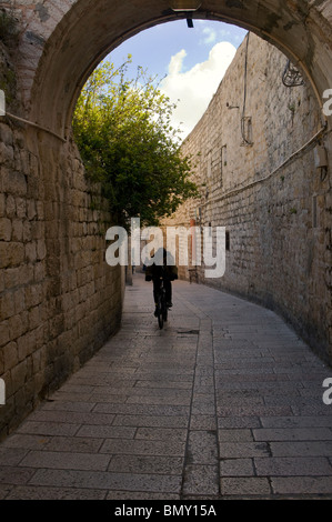 A bicycler passing through St James street in the Armenian quarter Old city of East Jerusalem Israel - Stock Photo