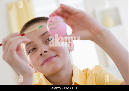 Young boy decorating an Easter egg - Stock Photo
