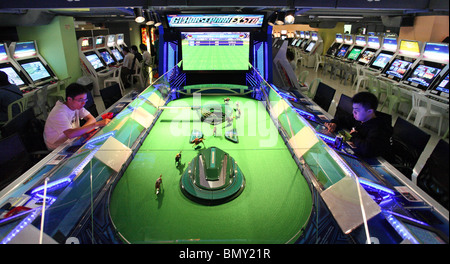People playing on horse-race slot machines in a casino, Hong Kong, China - Stock Photo