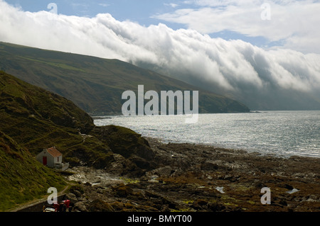 Orographic cloud pouring off the hills above Niarbyl Bay, Isle of Man, British Isles - Stock Photo