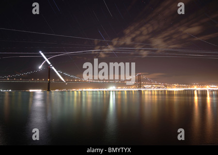 The path of the crescent moon as it sets over the Ponte 25 de Abril bridge in Lisbon, Portugal. - Stock Photo
