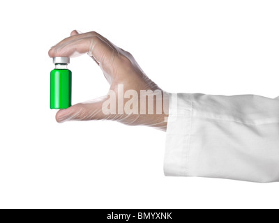A doctor holds a vial full of green liquid with his latex gloves on. Isolated on white. - Stock Photo