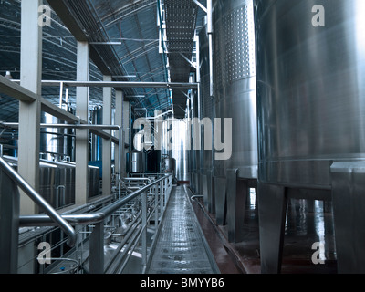 Stainless steel wine vats in a row inside the winery. - Stock Photo