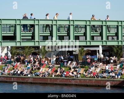 People crossing modern footbridge across Spree River with busy riverside bar to rear in Berlin Germany - Stock Photo