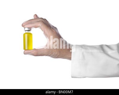 A doctor holds a vial full of yellow liquid with his latex gloves on. Isolated on white. - Stock Photo