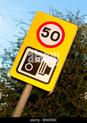 Speed camera warning sign and 50mph speed limit notice on a British road - Stock Photo
