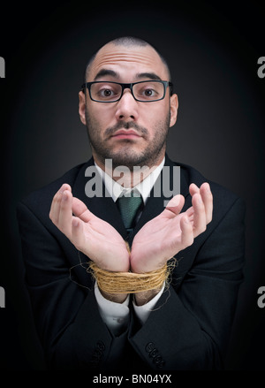 A man on a suit shows his tied hands with a puzzled expression. - Stock Photo
