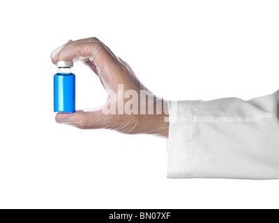 A doctor holds a vial full of blue liquid with his latex gloves on. Isolated on white. - Stock Photo