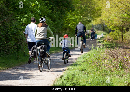 Family group cycling together on foot path - Stock Photo