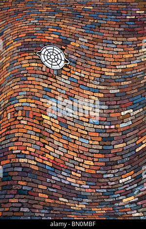 Warped image of cast iron utility handhole in colorful brick paved street at Ybor City area of Tampa, Florida - Stock Photo