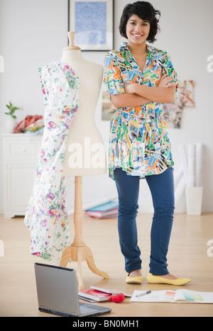 Hispanic woman standing with dressmaker's dummy - Stock Photo