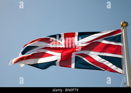 Union jack flag flying on a pole in the wind against a blue sky - Stock Photo