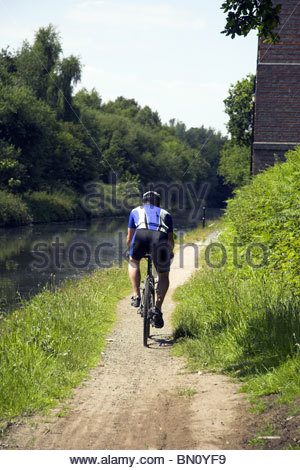 A cyclist on National Cycle Route 5, that is also the towpath for the Birmingham to Wolverhampton canal in the West - Stock Photo
