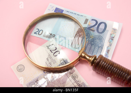 €20 and £20 notes under a magnifying glass - Stock Photo