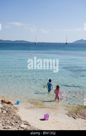 A brother and sister go netting for fish and shrimps on Formentor beach in Mallorca, Spain 2010 - Stock Photo
