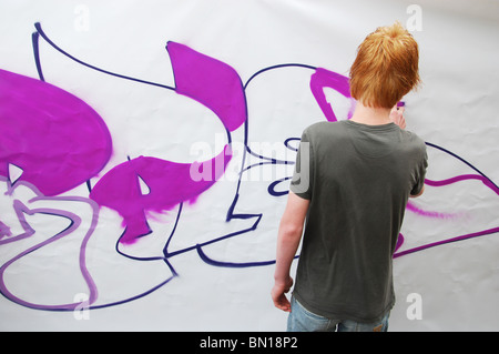 adolescent teenager applying graffitti - Stock Photo