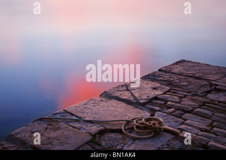 A coil of rope lying on a stone jetty next to the sea in Swanage, Dorset. The water is calm and lit by the setting - Stock Photo
