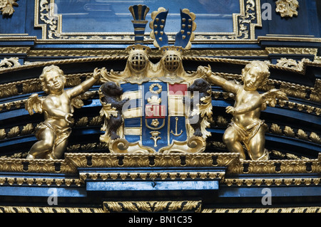 Golden image of cherubs flanking the Royal Coat of Arms, Church of the Infant Jesus of Prague - Stock Photo